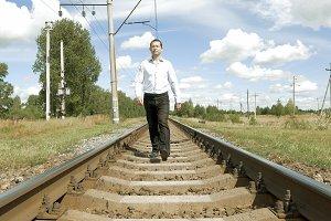 Man walking along railway tracks toward camera
