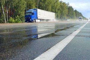 Traffic on wet road highway with mist splash