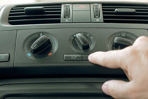 Male hand turning switch of car air conditioner