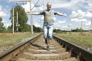 Smiling man jumping dancing on the railway tracks