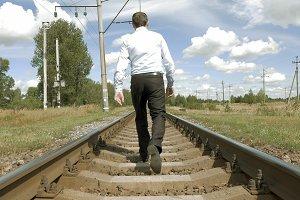 Man walks along railway tracks in the countryside