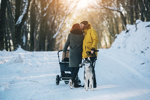 family walking with the stroller in the winter