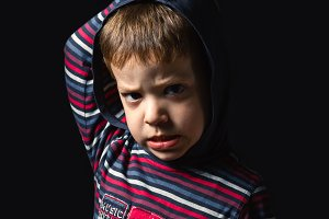 Angry boy with hoodie standing over black background