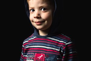 Boy with hoodie standing over black background