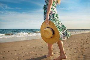 Barefoot woman walking on sea beach