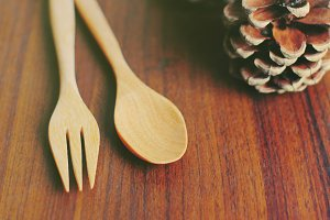 Wooden spoon and fork with pine cone