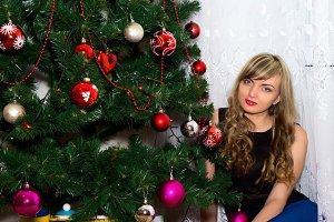 Beautiful blonde near Christmas tree.