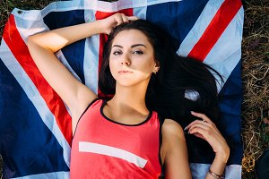 Young beautiful brunette girl posing with a British flag in autumn park