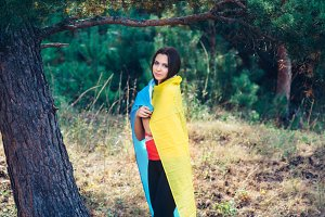 Beautiful brunette model posing in a park with  flag of Ukraine