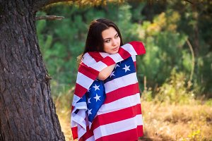 Beautiful model poses with the flag of the USA in the summer park