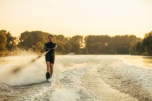Male water skiing behind a boat