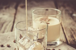 Pouring coffee liqueur in glasses with ice and beans