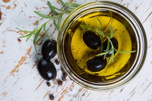 Olive oil with maslines on wood background
