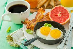 Summer breakfast - eggs, bacon, toast, jam, coffee, juice