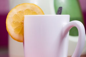 white cup with piece of lemon
