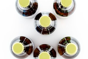 Six bottles of beer with caps facing camera