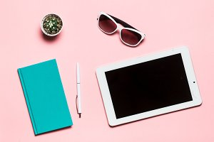 White tablet, pen, glasses, mint diary, and cactus on pink background. flat lay, top view.