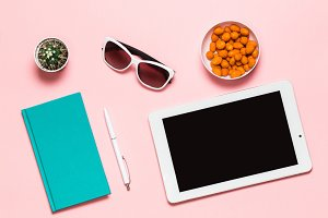 Workspace mockup White tablet, pen, glasses, mint diary, and cactus on pink background. flat lay, top view.