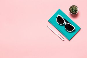 Creative flat lay photo of workspace desk with aquamarine notebook, eyeglasses, cactus copy space pink background, minimal style