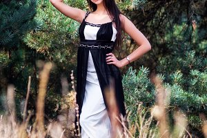 Graceful charming brunette model posing in black dress in coniferous park