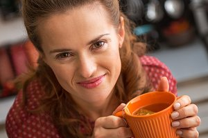 happy young housewife drinking tea in kitchen
