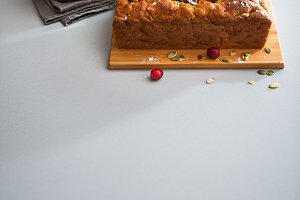 Woman's hands holding a baking tin with cranberry and seed loaf
