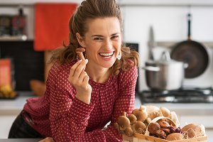 Happy young housewife with basket with mushrooms in kitchen