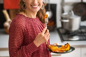 Closeup on young woman eating baked pumpkin in kitchen