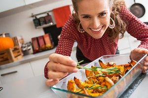 Smiling elegant woman preparing roasted pumpkin dish