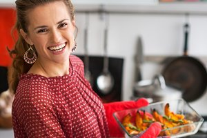 Portrait of happy young housewife holding baked pumpkin