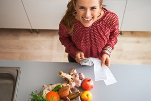 Happy young housewife with money and grocery shopping checks after shopping on local market