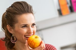 Young housewife with purchases from local market eating apple