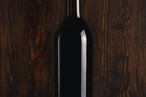 Glass bottle of wine on the black background