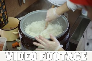 The chef mixes the cooked rice