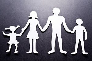 Cardboard figures of the family on a black background. The symbol of unity and happiness.
