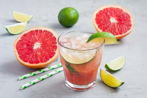 Cold pink cocktail with fresh grapefruit, lime and ice cubes