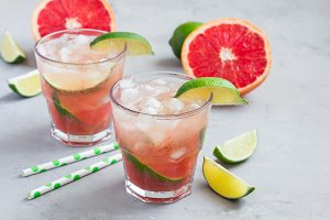 Cold pink cocktail with fresh grapefruit, lime, copy space