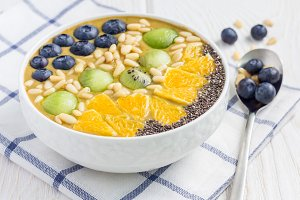 Breakfast smoothie bowl topped with berries, fruits, nuts and seeds