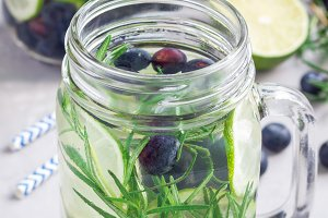 Healthy infused water with fresh blueberry, lime and rosemary, vertical