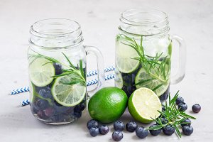 Healthy infused water with fresh blueberry, lime and rosemary, horizontal