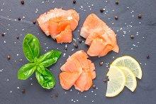 Smoked salmon filet with lemon and basil, top view, horizontal
