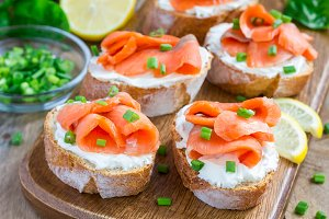 Sandwich with smoked salmon and cream cheese, wooden board, horizontal