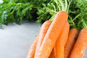 Fresh carrots on gray background. Closeup