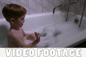 The little boy bathes in a bath