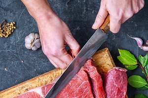 Woman in the kitchen is cutting beef