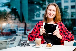 Young happy woman showing a tablet sitting in cafe