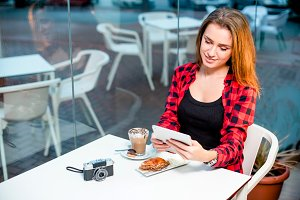 Young happy woman with a tablet sitting in cafe