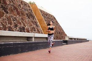 Young woman running at shore