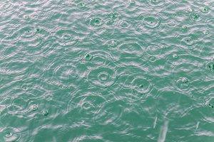 Rain drops in blue water on lake.