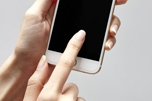 Girl's hand holding a modern smartphone and pointing with figer